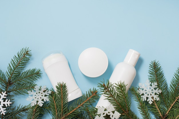 Winter cosmetics antiperspirant, gel and cream with green tree and snowflakes on blue , copyspace.  body care