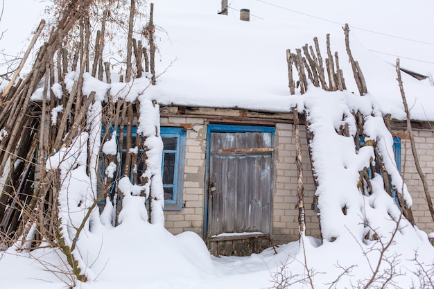 Winter countryside landscape, dilapidated abandoned ruined building covered in snow.