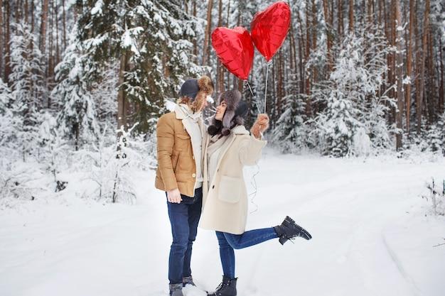 사랑에 겨울 커플입니다. 소년과 소녀는 겨울에 포옹 눈과 풍선 요정 숲입니다.