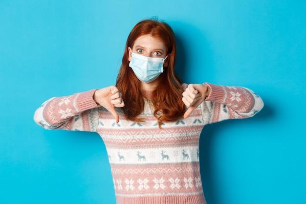 겨울, covid-19 및 유행성 개념. 파란색 배경 위에 서있는 당신과 반대, 싫어하는 엄지 손가락 다운을 보여주는 의료 마스크에 불쾌한 빨간 머리 여자.