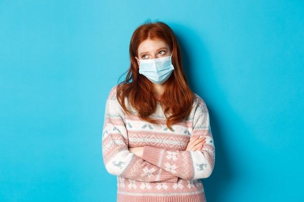 冬、covid-19およびパンデミックの概念。フェイスマスクで無知な赤毛の10代の少女、目を転がし、面白がっていないように見え、胸に腕を組んで嫌がり、青い背景の上に立っています。