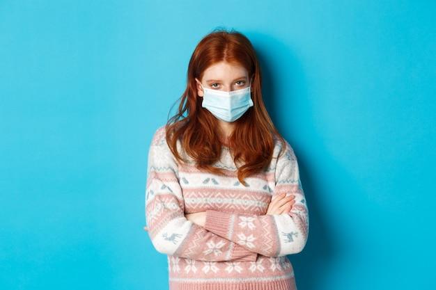 겨울, covid-19 및 전염병 개념. 의료용 마스크를 쓴 회의적인 빨간 머리 소녀, 가슴에 팔짱을 끼고 카메라를 쳐다보며 화난 표정으로 파란 배경 위에 서 있다