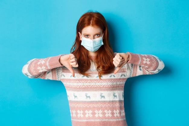 冬、covid-19およびパンデミックの概念。不承認を示し、嫌いで親指を下ろし、青い背景の上に立っているフェイスマスクの動揺して怒っている赤毛の女の子。