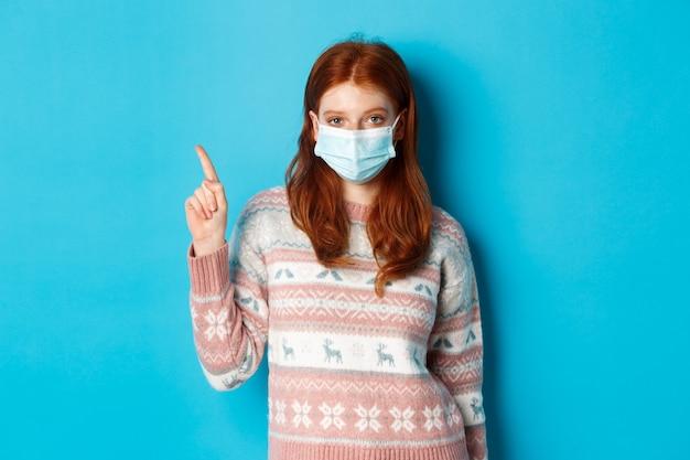 겨울, covid-19 및 격리 개념. 얼굴 마스크에 아름 다운 빨간 머리 소녀, 파란색 배경 위에 서있는 광고를 보여주는 왼쪽 상단 모서리 로고에서 손가락을 가리키는.