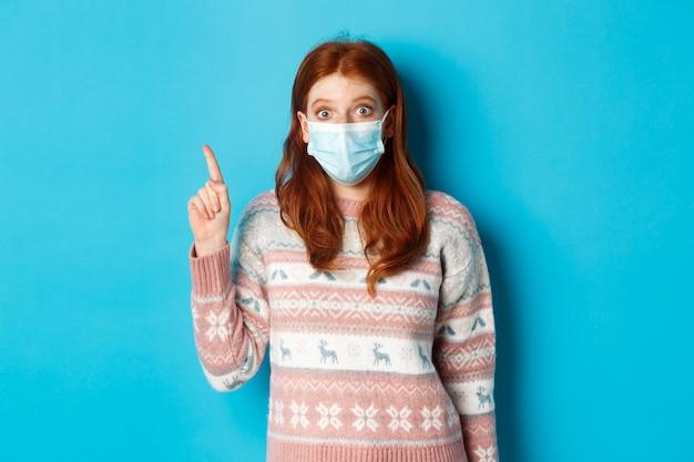 겨울, covid-19 및 검역 개념. 스웨터와 얼굴 마스크를 쓴 흥분한 빨간 머리 여성, 왼쪽 위 모서리 프로모션에 손가락을 가리키고 로고를 표시하고 파란색 배경 위에 서 있습니다.