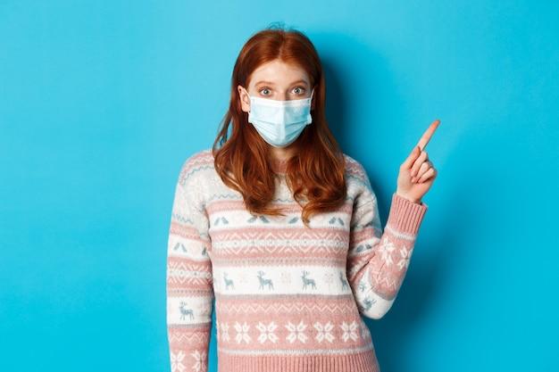 冬、covid-19および検疫の概念。医療マスクピッキング製品に興味をそそられた赤毛の女の子、右上隅のプロモーション、青い背景を見て指しています。