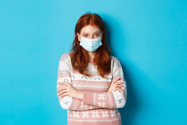 겨울, covid-19 및 검역 개념. 스웨터와 의료용 마스크를 쓴 회의적인 빨간 머리 소녀, 가슴에 팔짱을 끼고 믿을 수 없다는 표정으로 쳐다보며 파란 배경 위에 서 있다