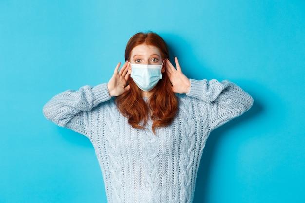 Зима, covid-19 и концепция социального дистанцирования. заинтригованная рыжая девушка в маске подслушивает, держась за руки возле ушей и прислушиваясь, стоит на синем фоне.