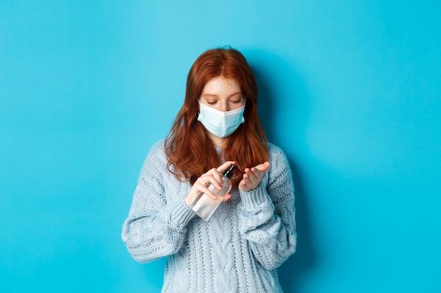 冬、covid-19および社会的距離の概念。フェイスマスクの赤毛の女子学生は、青い背景に立って、消毒剤を使用して、消毒剤で手をきれいにします。