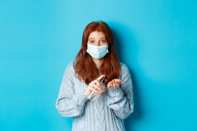 Зима, covid-19 и концепция социального дистанцирования. удовлетворенная молодая рыжая женщина в маске показывает хорошо, хорошо жесты и смотрит влево на промо, синий фон.