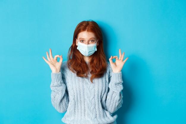 冬、covid-19および社会的距離の概念。フェイスマスクで満足している若い赤毛の女性は、大丈夫、大丈夫なジェスチャーを示し、満足しているように見え、青い背景に立っています。