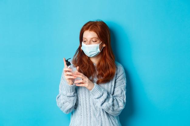 겨울, covid-19 및 사회적 거리 개념. 얼굴 마스크를 쓴 젊은 빨간 머리 여성은 소독제로 손을 닦고, 손 소독제로 소독하고, 파란색 배경에 서 있습니다.
