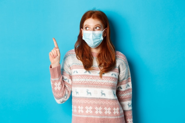 Winter, covid-19 and quarantine concept. curious redhead girl in medical mask picking product, looking and pointing at upper left corner promo, blue background