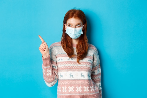 Winter, covid-19 and quarantine concept. image of cute redhead girl in face mask and sweater, pointing upper left corner, picking product, standing over blue background