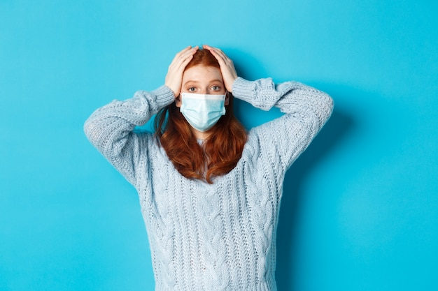 Winter, covid-19 and social distancing concept. troubled redhead girl in face mask staring distressed, holding hands on head in panic, standing over blue background