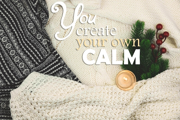Winter cozy background and inspiration, woolen and knitted sweater, composition with text you create your own calm. high quality photo