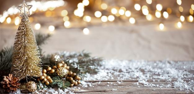 お祭りの装飾の詳細、木製のテーブルとボケの雪と冬の居心地の良い背景。家庭でのお祝いの雰囲気のコンセプト。