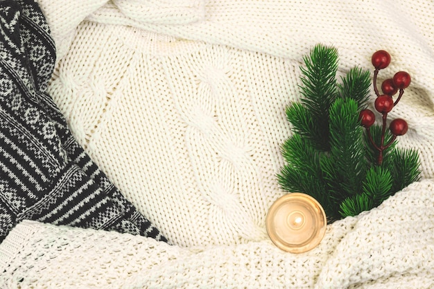 Winter cozy background, woolen and knitted sweater, fir branch with red berries and candle, composition with copy space. high quality photo