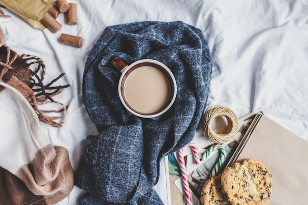 Winter cozy . cup with coffee , cookies, gift , fir branch, plaid on the bed