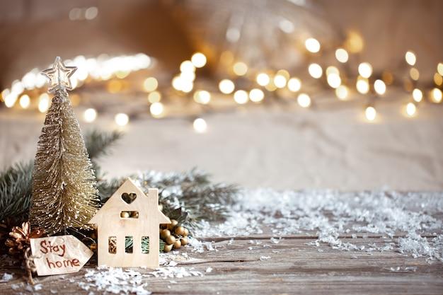 冬の居心地の良いお祭りの装飾の詳細、木製のテーブルとボケの雪。家にいる