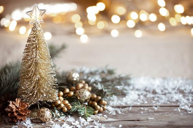 冬の居心地の良いお祭りの装飾の詳細、木製のテーブルとボケの雪。