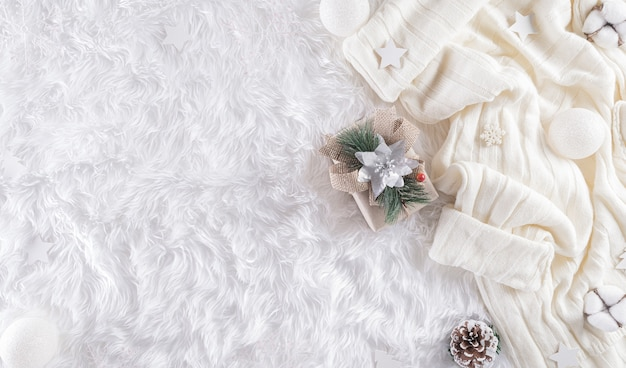 Winter cozy wall with cup of coffee, warm sweater, gift box, cotton flower and christmas ball on wool carpet wall, top view with copy space.