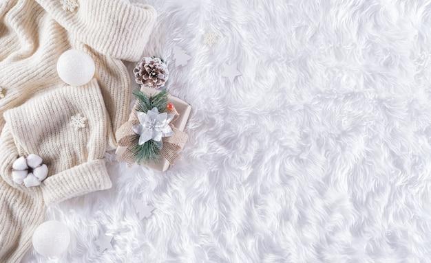 一杯のコーヒー、暖かいセーター、ギフトボックス、綿の花、ウールのカーペットの壁にクリスマスボール、コピースペースのある上面図のある冬の居心地の良い壁。