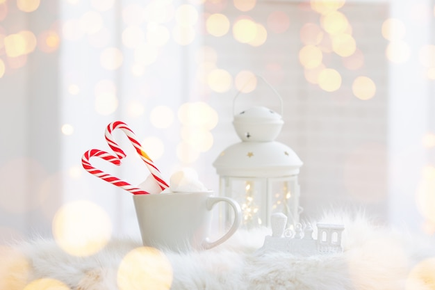 Winter cup of hot drink with a candy cane on white wooden background
