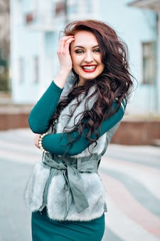 Winter cute woman fashion. smiling woman wearing sweater fur vest. stylishly dressed beautiful young woman in a fur vest walks at the street