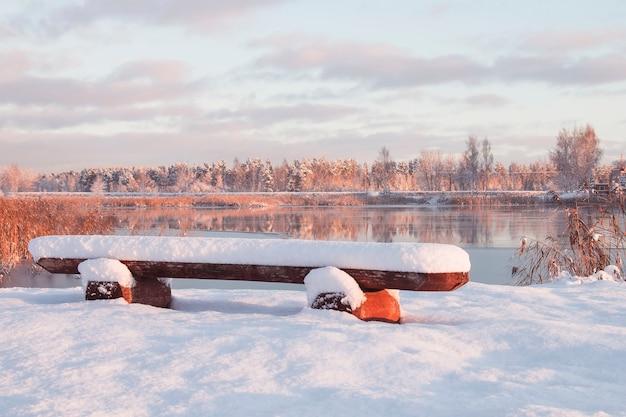 Зимний рассвет, скамейка на берегу реки, заснеженные деревья