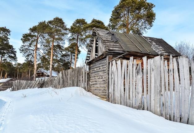 Зимний день в деревне. у леса стоит старый сарай и деревянный забор.