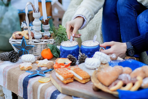 Winter decor sweet table. mugs with cocoa. people hands