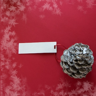Зимнее украшение сосновая шишка с этикеткой на снежном красном фоне