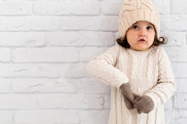 冬の壁の横にある小さな女の子