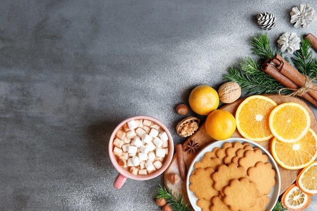 Зимний напиток. плоский слой кружки с горячим шоколадом или какао и небольшими кусочками зефира, имбирного печенья, палочки корицы, шишек, веточек ели, мандарина, орехов на черном фоне.