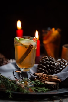 Winter drink with cinnamon stick and apple slice in christmas table