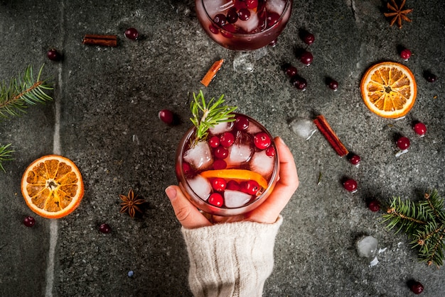Winter drinks. girl drinks cold cocktail with cranberries, orange, rosemary, with spicescinnamon, anise and ice, on a dark stone table,  top view, hands