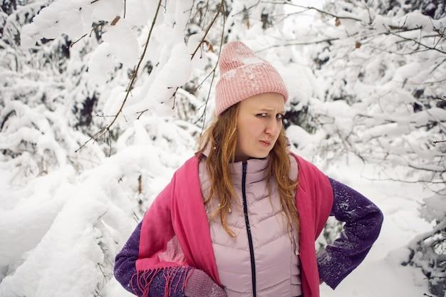 雪の森で眉をひそめるピンクの帽子の冬の感情的な女性