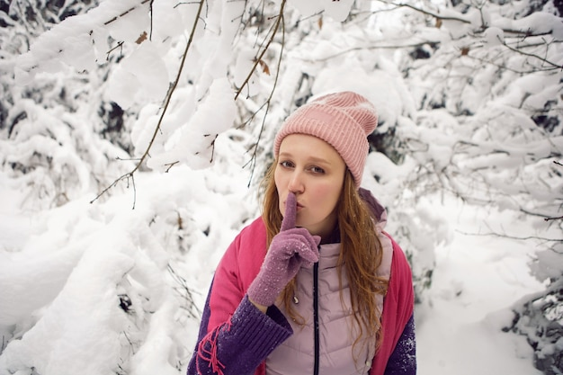雪の森で楽しんでいるピンクの帽子の冬の感情的な女性