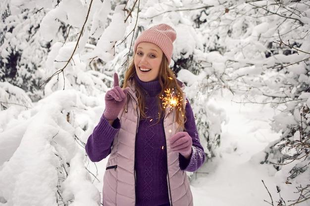 雪と森の中で楽しい線香花火を持っているピンクの帽子の冬の感情的な女性