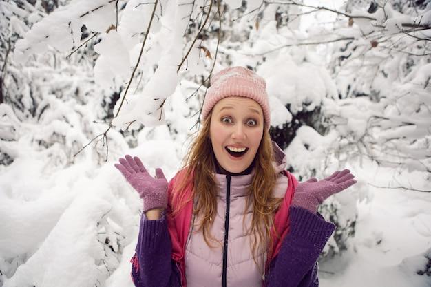 雪の森で楽しい驚きを持っているピンクの帽子の冬の感情的な女性
