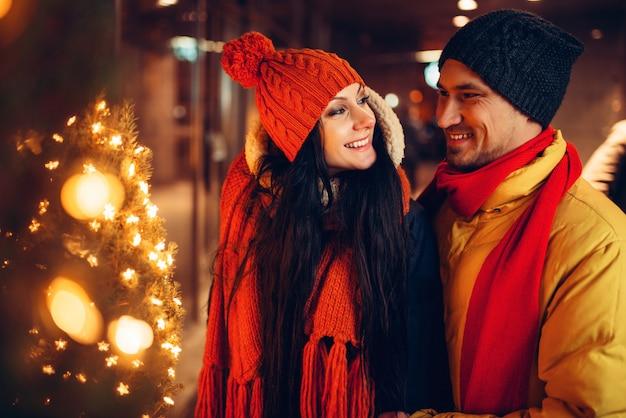 冬の夜、愛のカップルの笑顔の街歩き。ロマンチックな会議、幸せな関係を持つ男女