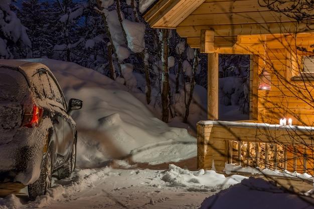 숲에서 겨울 저녁입니다. 많은 눈. 검은색 자동차는 조명이 있는 현관이 있는 목조 주택 근처에 서 있다