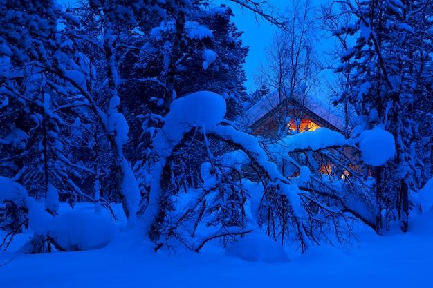 森の中で冬の夜。雪がいっぱいある。バックグラウンドで照明付きのコテージ