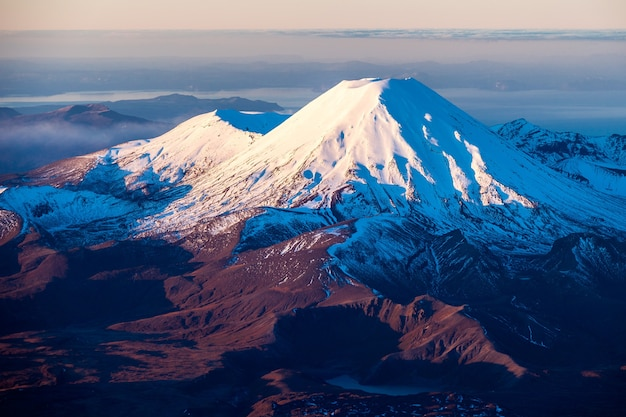 Зимний вечерний свет на горах нгаурухо и тонгариро. озеро нижняя тама на переднем плане. национальный парк тонгариро, новая зеландия