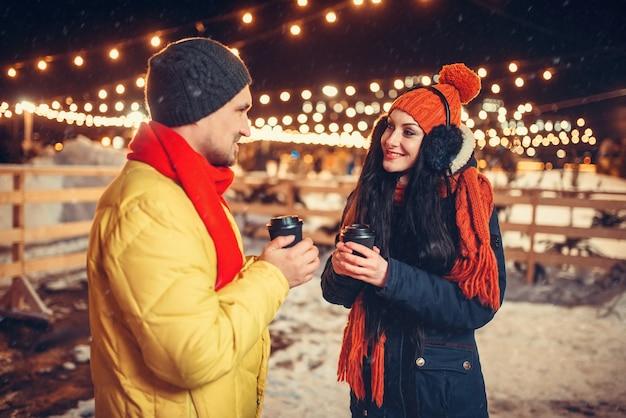 冬の夜、愛のカップルは屋外でコーヒーを飲みます