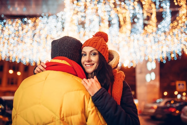 Зимний вечер, влюбленная пара обнимается на улице. мужчина и женщина, имеющие романтическую встречу, счастливые отношения