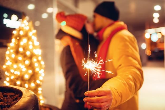冬の夜、カップルが屋外でキスが大好きです。街でロマンチックな会議を持つ花火を持つ男女