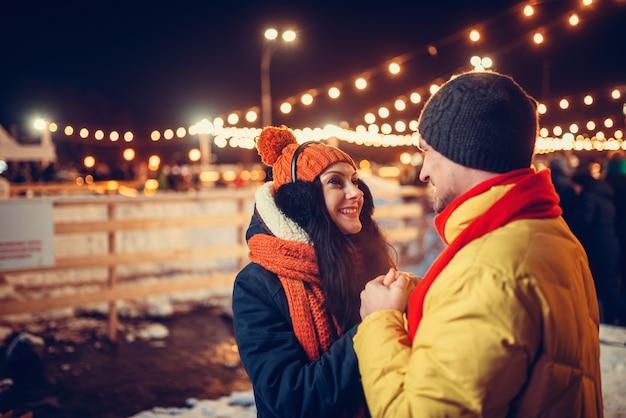 冬の夜、野外を歩いている愛のカップル