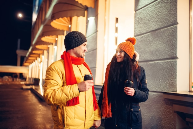 冬の夜、通りを歩いてコーヒーが大好きなカップル。男と女のロマンチックな会議